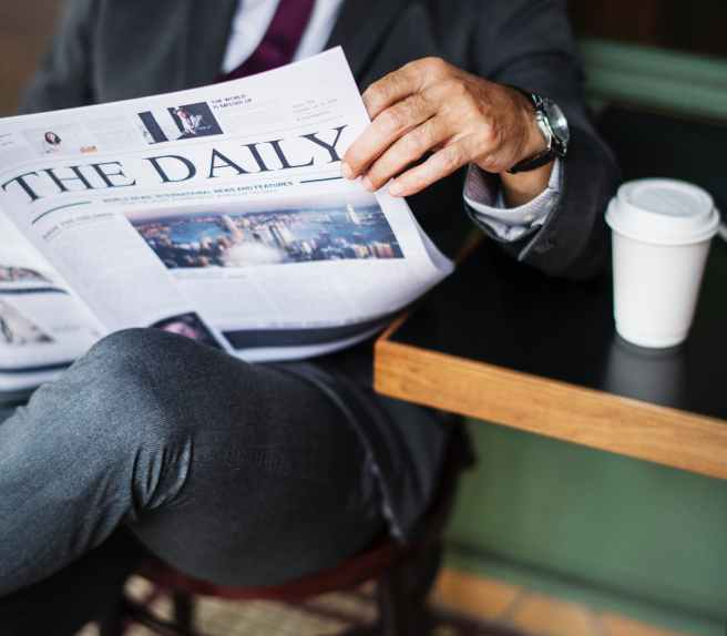 photography of a person reading newspaper