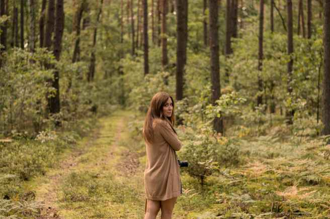woman standing in the middle of the forest