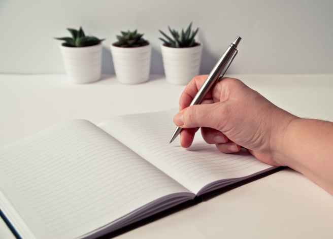 person holding silver retractable pen in white ruled book